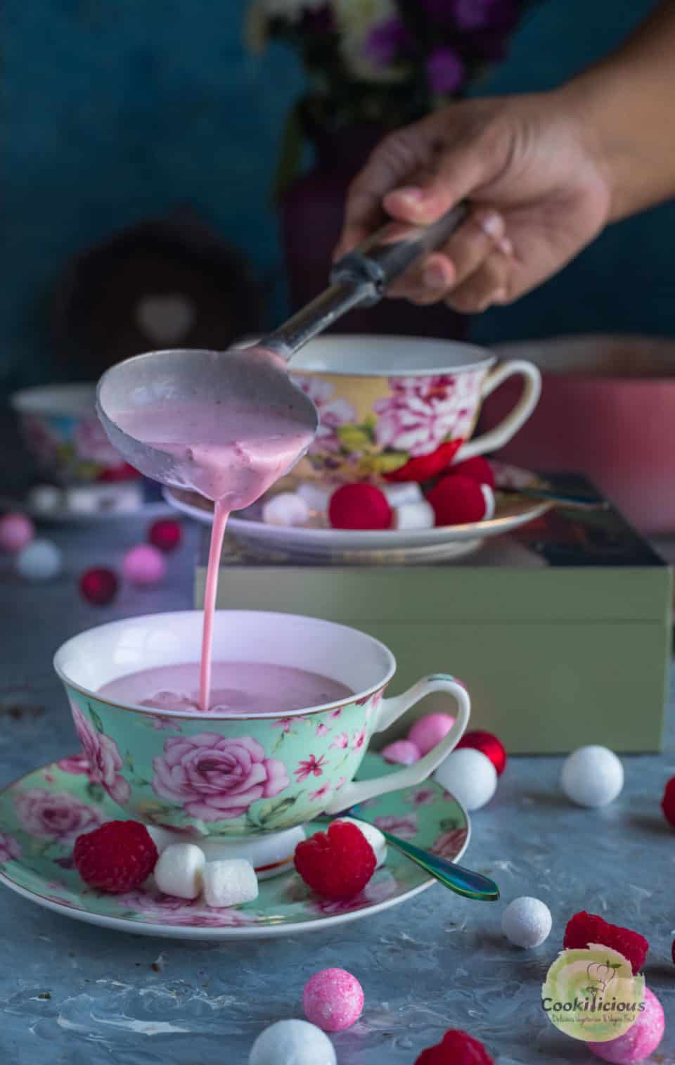 a hand pouring Vegan Raspberry Rose Hot Chocolate into a teacup