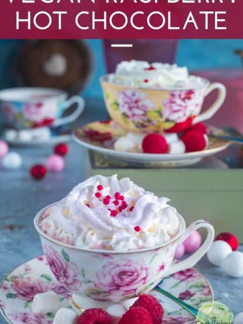 Vegan Raspberry Rose Hot Chocolate served in teacups with whipped cream on top and text at the top