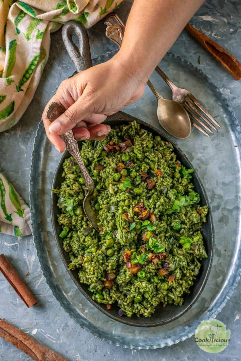 a hand digging into a plate of Spinach Garlic Rice with a spoon