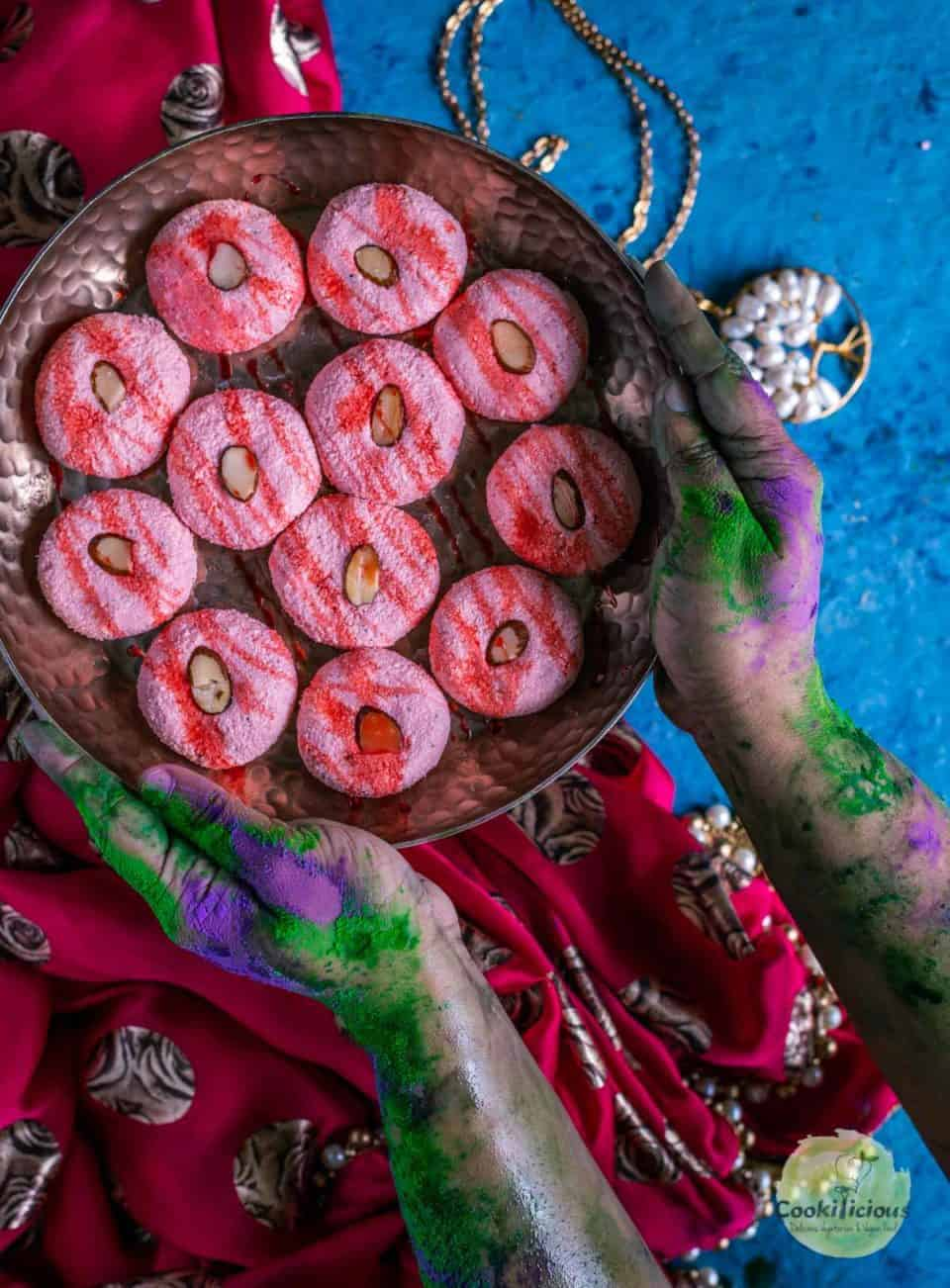 a set of colored hands holding a plate full of Rose Sandesh - Bengali Sweet Recipe