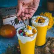 one hand digging a spoon into a glass of mango milkshake