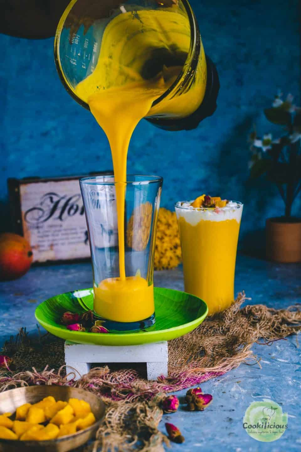 Mango milkshake being poured into a glass from a blender jar