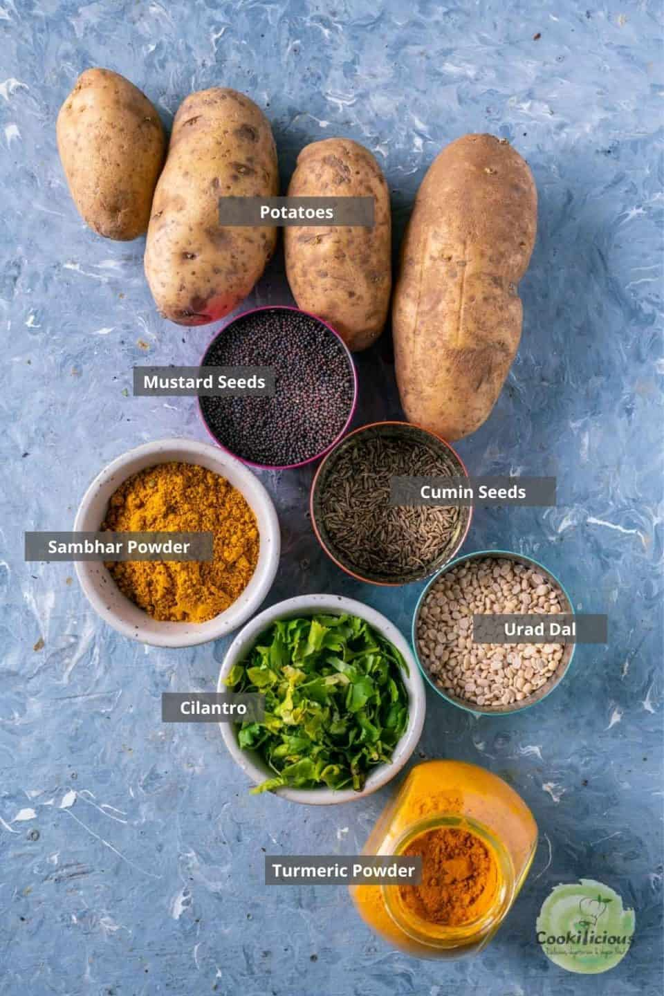 all the ingredients needed to make South Indian Spicy Potato Curry placed on a table with labels on them