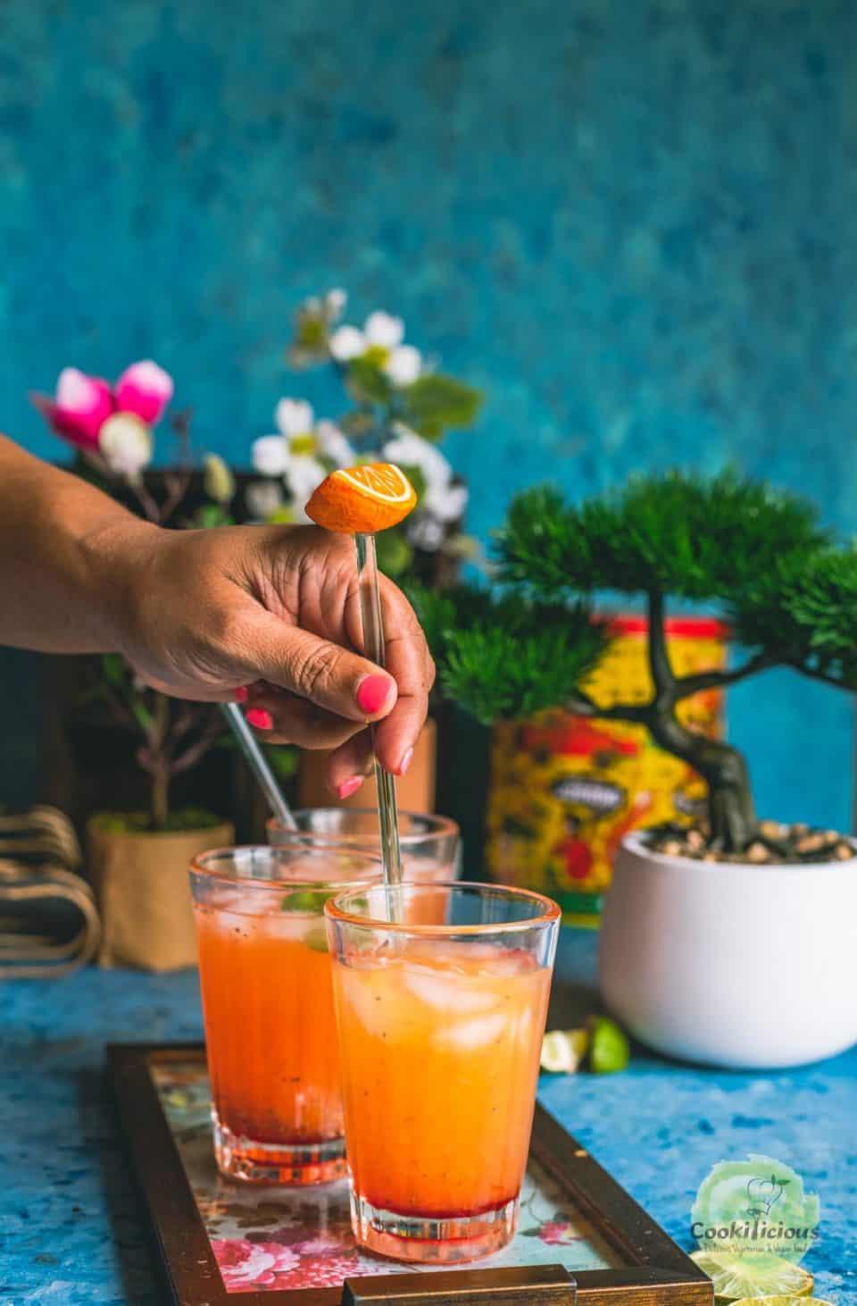 a hand stirring a glass of Rose Lemonade with a stirrer