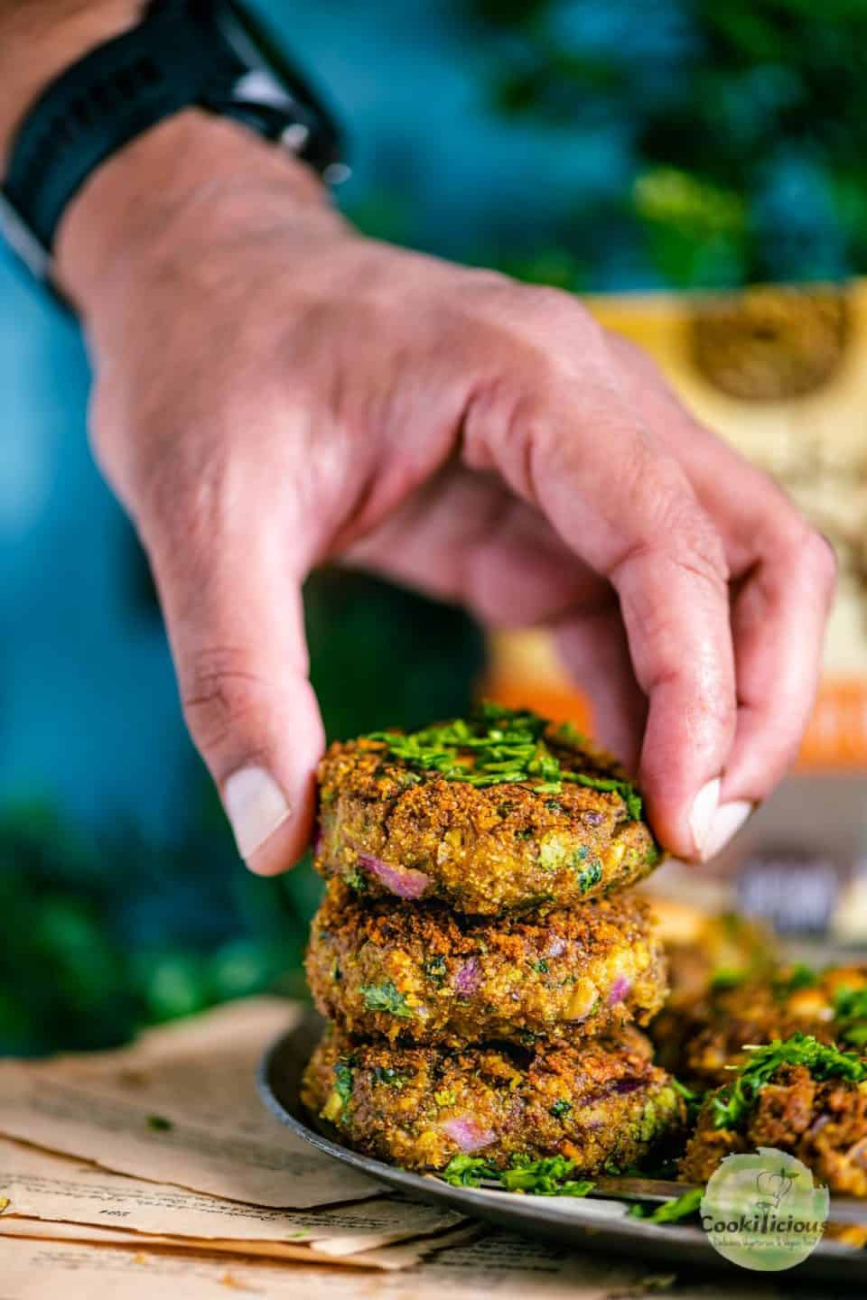 a hand picking up one chickpea patty from a stack