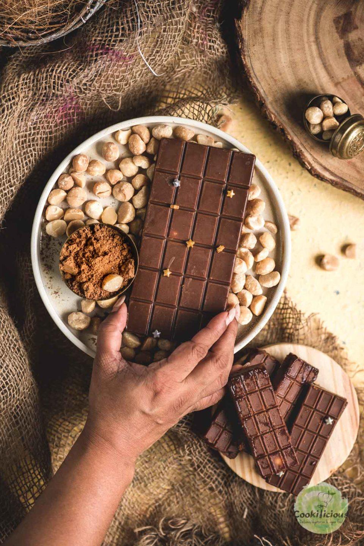 a hand reaching out to grab a Vegan Chocolate Macadamia Bar