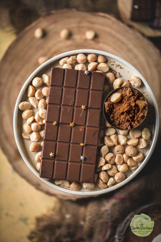 Vegan Chocolate Macadamia Bar served on a platter with macadamia nuts around it