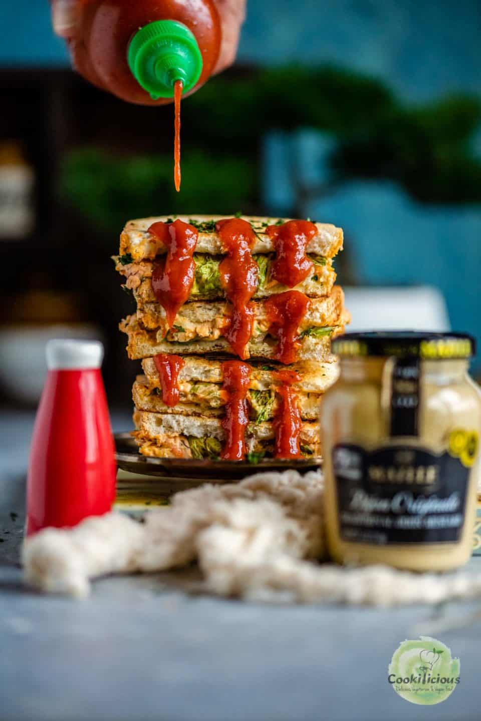 sauce being poured on a stack of Veggie Sandwiches