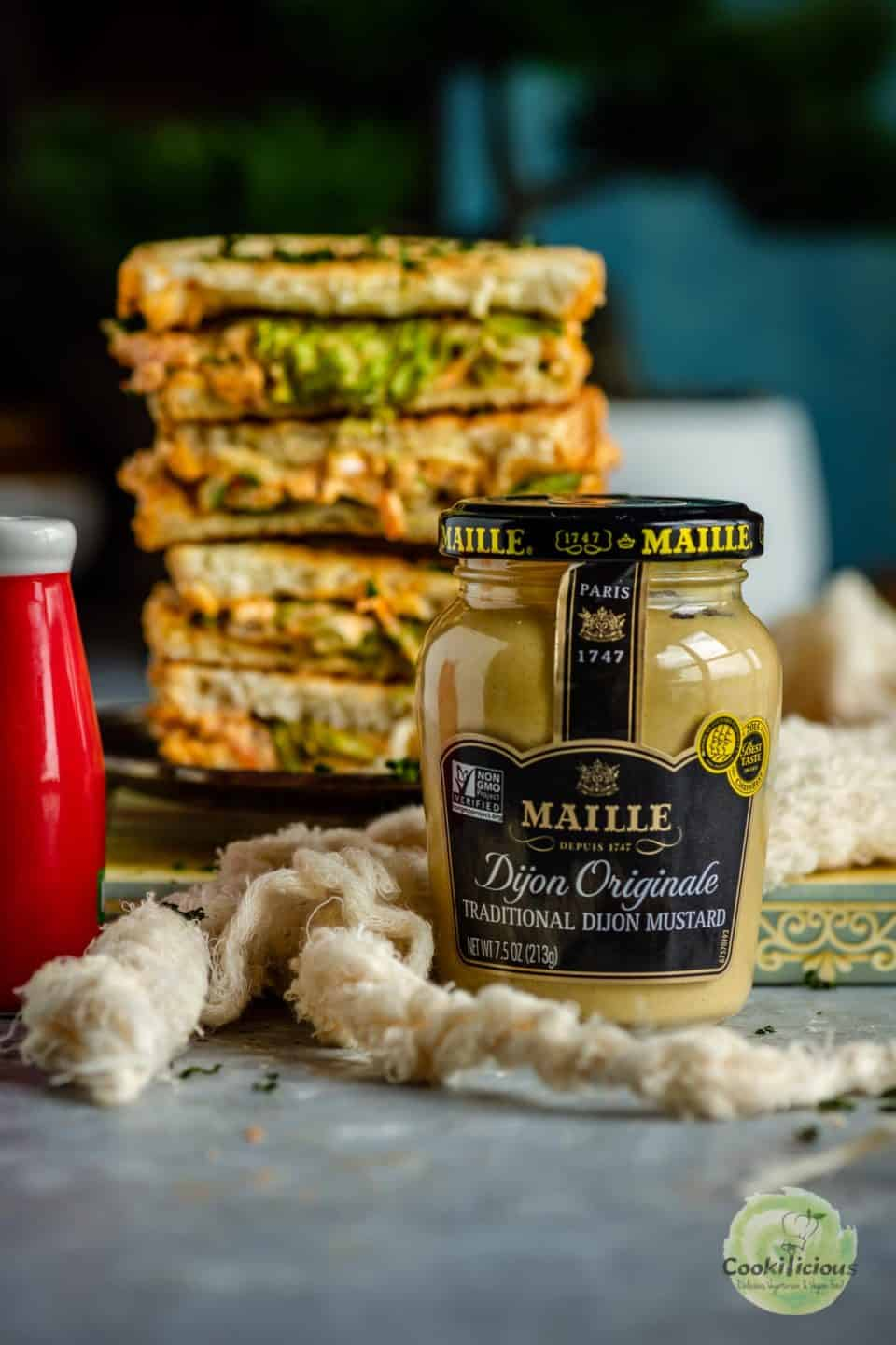 Veggie Sandwich stack with a maille mustard jar in front