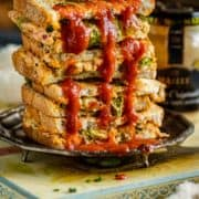 a stack of Veggie Sandwiches with red sauce over it