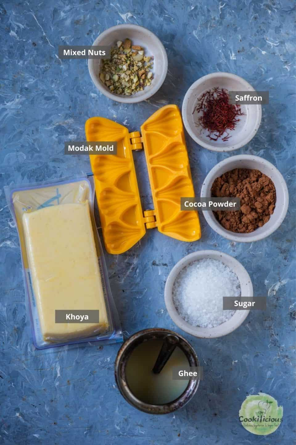 all the ingredients required to make Chocolate Mawa Modak placed on a table with labels on them
