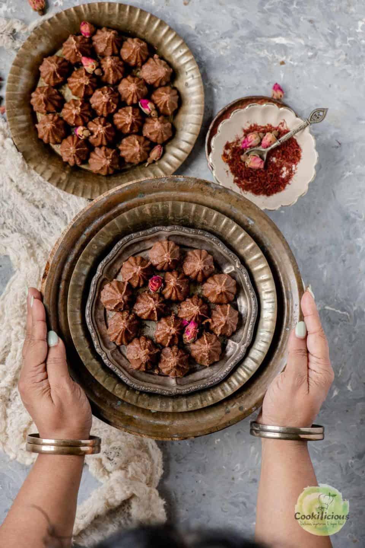 a set of hands serving Chocolate Mawa Modak in a plate