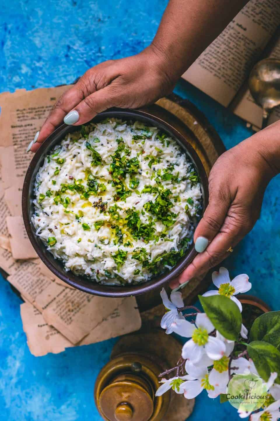 a set of hands holding a bowl filled with curd rice