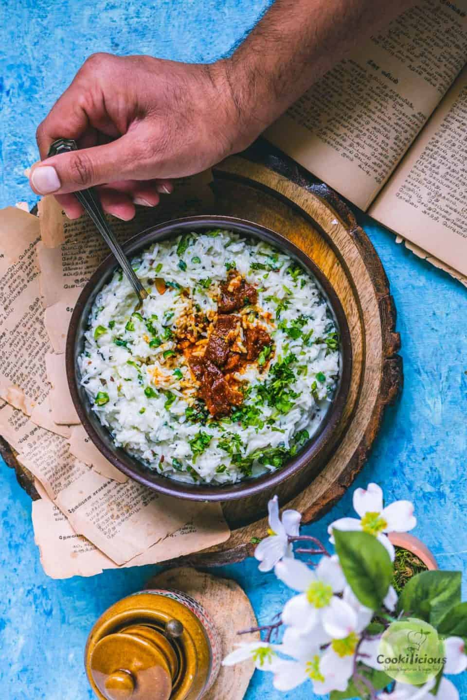 a hand digging into a bowl of dahi bhaat with a spoon