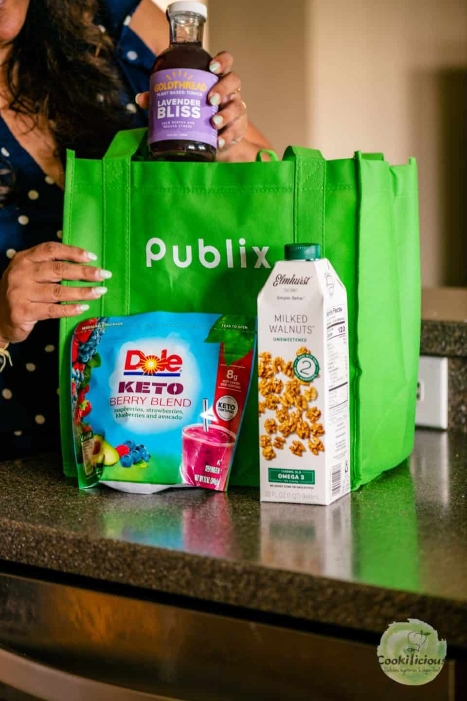A lady removing grocery items from Publix shopping bag