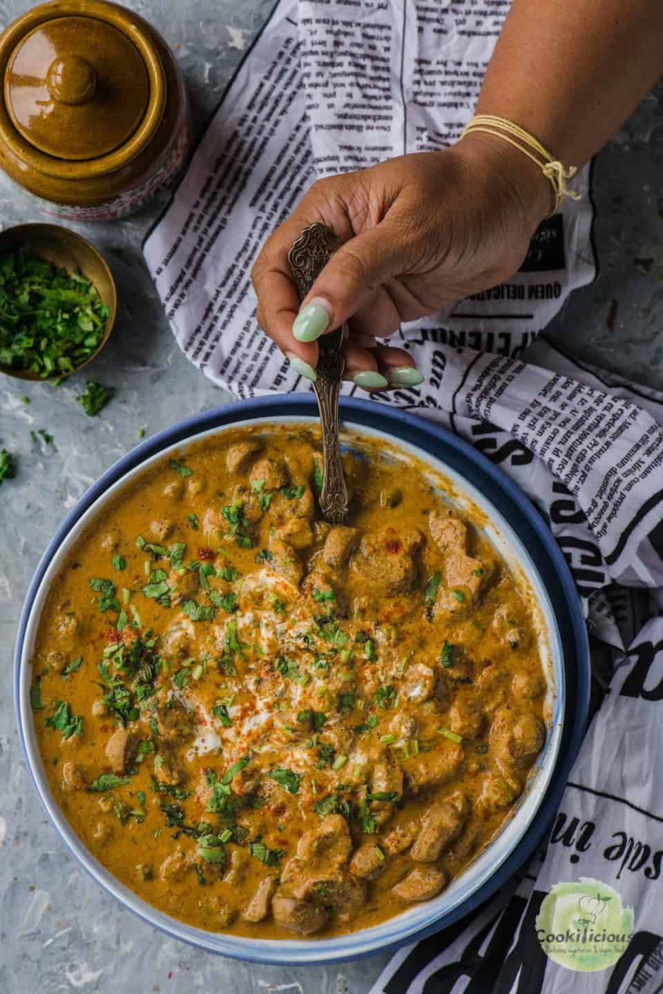 a hand holding a spoon and digging into a bowl of Mushroom Masala