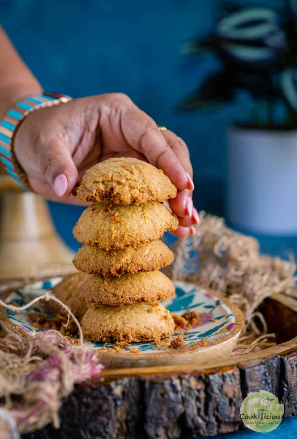 a hand picking up one Whole Wheat Ghee Cookie from a stack