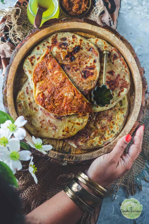a hand holding a tray of sweet potato puran poli